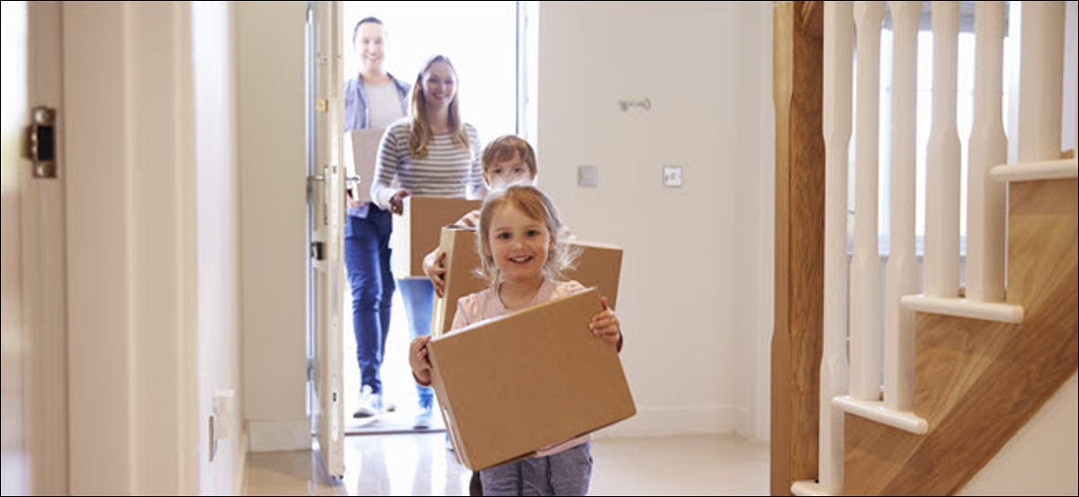 A happy family carrying boxes into a home.