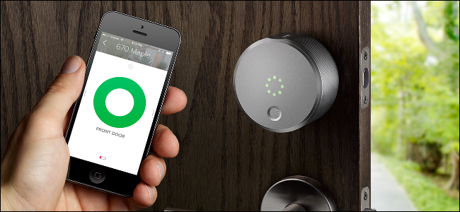 A man's hand holding an iPhone showing the August Smart Lock app and opening a door with an August Smart lock on it.