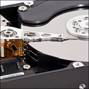 An open hard drive case showing the physical platters and actuator arm
