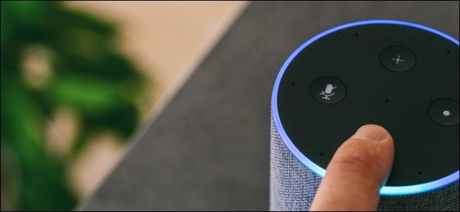 A finger touching an Amazon Echo speaker.