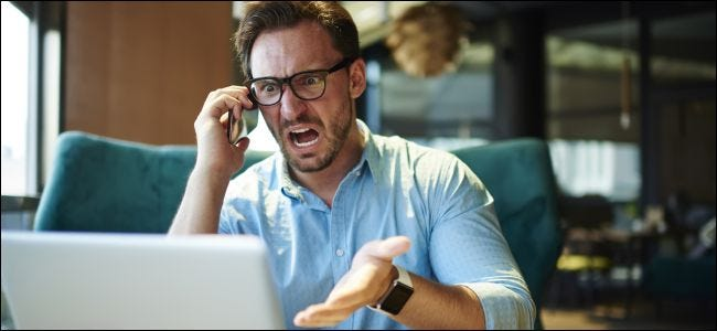 Upset man on cell phone gesturing at a laptop.