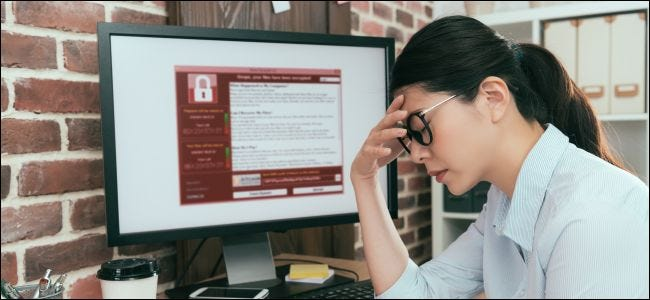 Woman who looks upset sitting next to a computer monitor with ransomware on it.