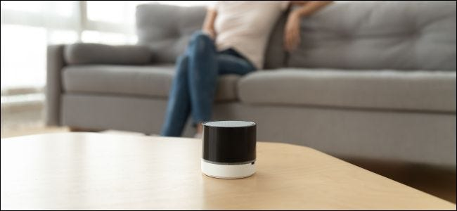 A wireless Bluetooth speaker on a coffee table in front of a woman sitting on a couch.