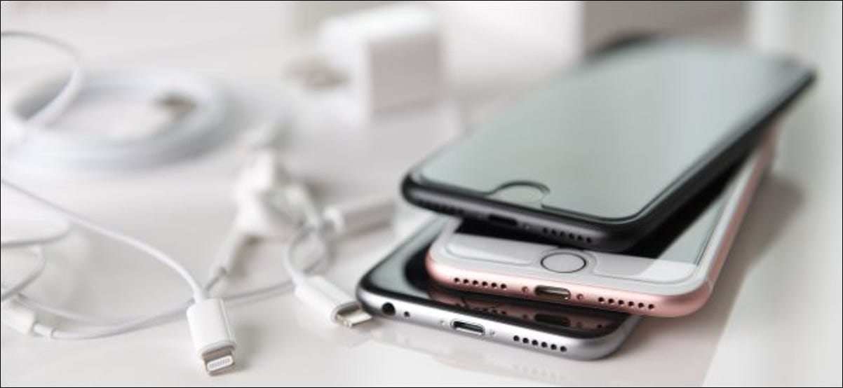 Old iPhones stacked on top of each other next to lightning cords.