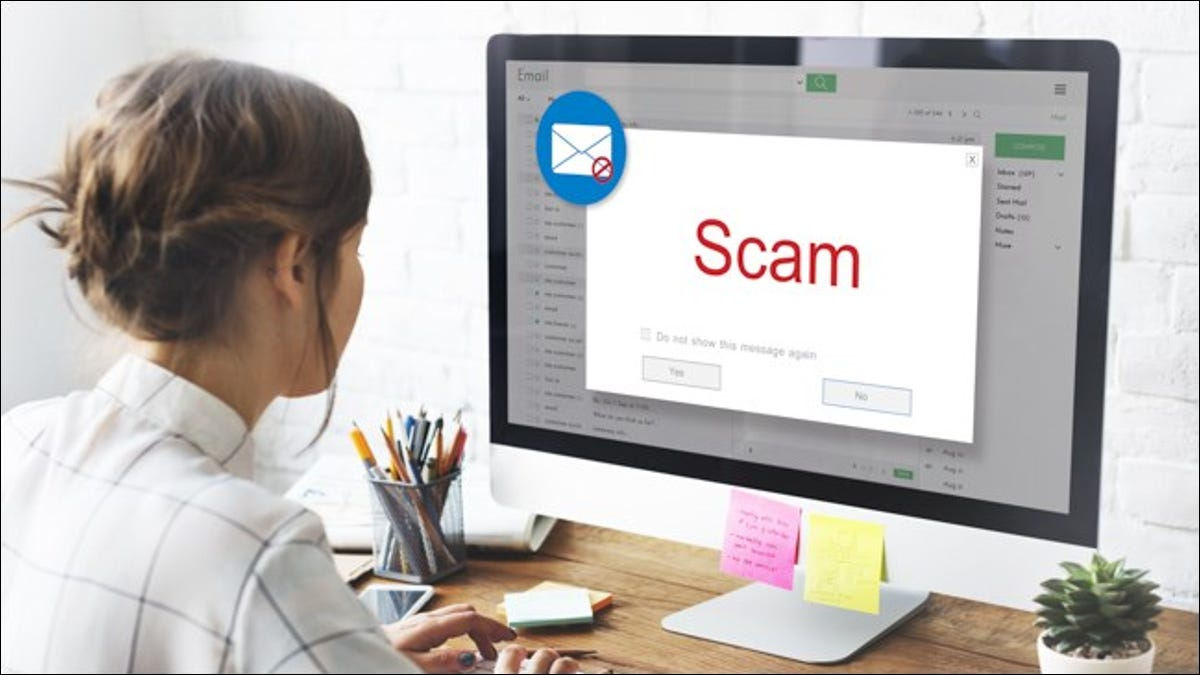 """A woman opening an email on her computer that says """"Scam."""""""