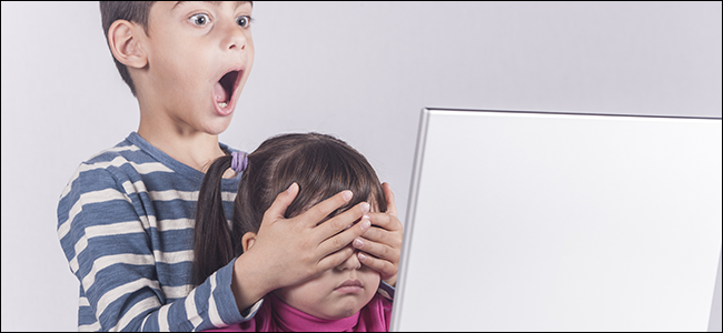 A little boy covers his sister's eyes at the computer.