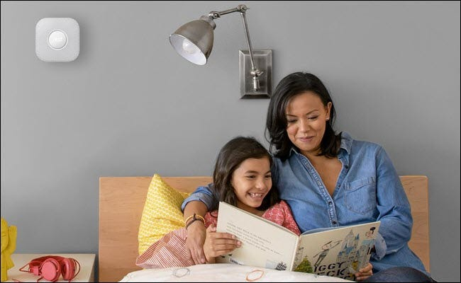 A mother and child reading a children's book in bed, with a Nest Protect mounted on the wall above their heads.
