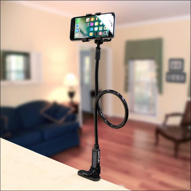 An iPhone on the Skiva Flexible Long Arm Cell Phone Clip Holder Stand attached to a countertop.