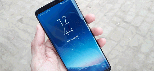 A hand holding a Samsung Galaxy S8 with the touch screen on showing the time and date.