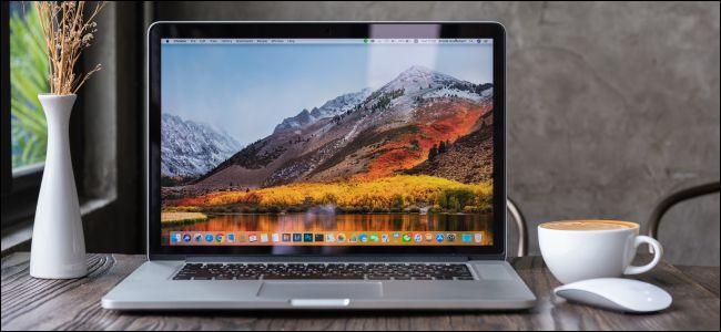 A MacBook laptop open on a wooden desk.
