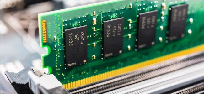 A RAM stick with bare modules sitting in a motherboard's RAM slot.