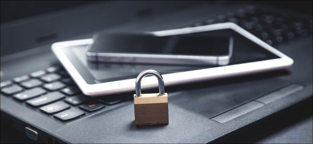 A padlock, smartphone, and tablet sitting on a laptop.