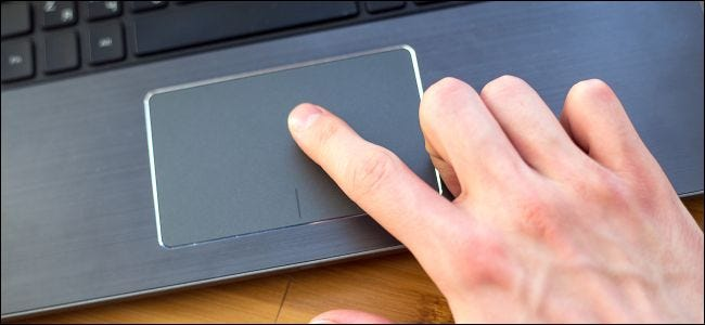 An index finger on a PC laptop's trackpad.