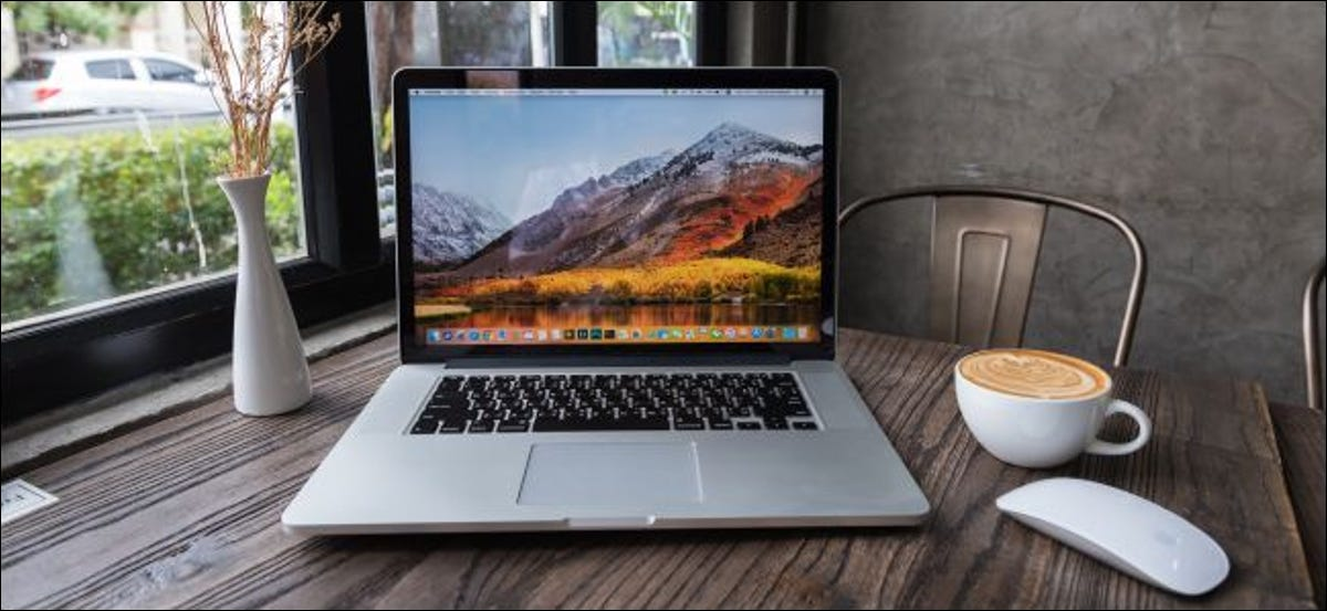 A MacBook and an Apple mouse with a cup of coffee on a wooden table.