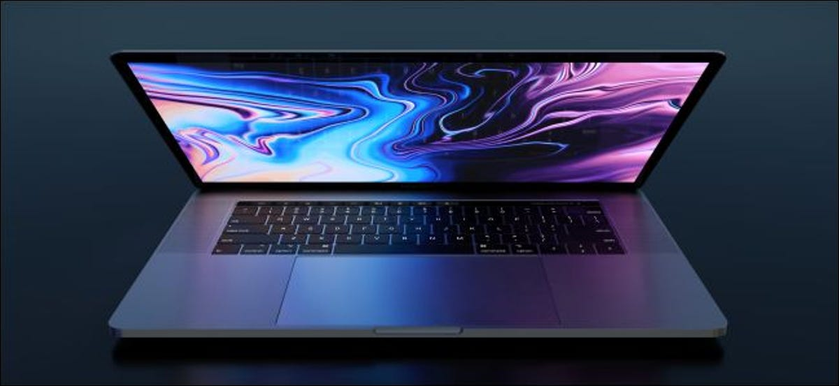 A MacBook Pro with the lid partially open and the screen glowing onto the keyboard.