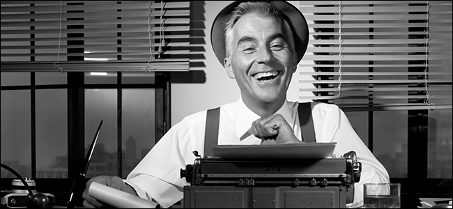 An old-timey reporter laughs behind a typewriter.