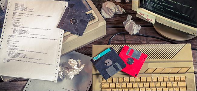 Un escritorio lleno de disquetes, hardware de computadora antiguo y papel arrugado.