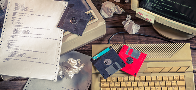 A desk full of floppy disks, old computer hardware, and crumpled up paper.