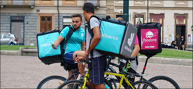 A couple of food delivery workers in Italy. They work for the Italian equivalents of companies like BiteSquad.