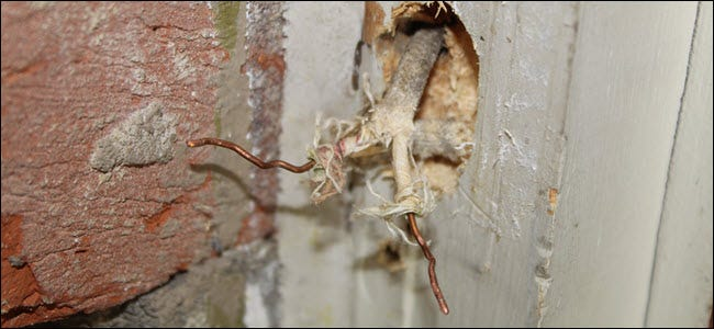 Dos cables expuestos que sobresalen de la pared.