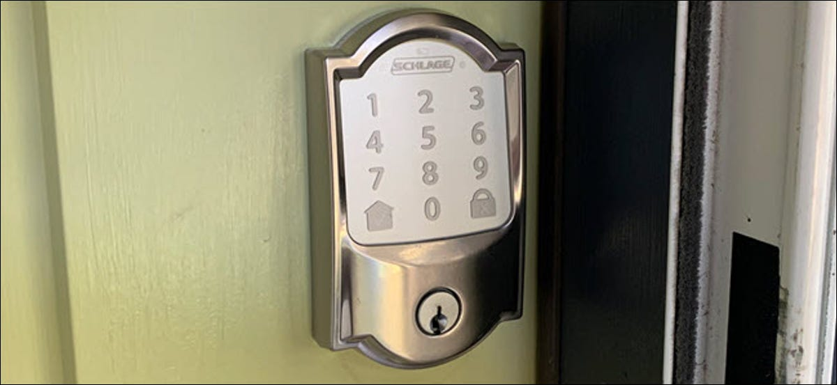A Schlage Encode satin style smartlock installed on a green door.