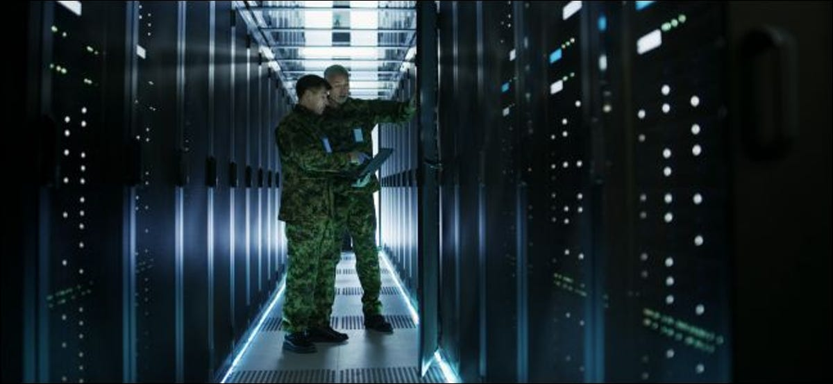 Two men in military uniforms in a data center.