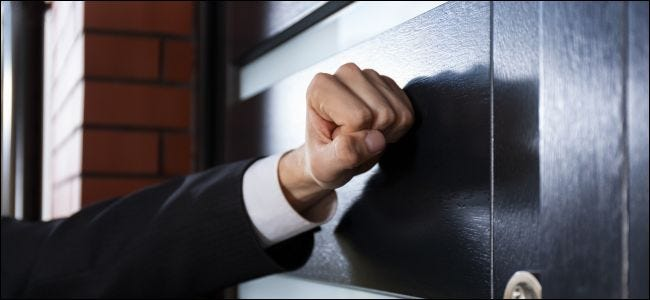 Hand knocking on a closed door.