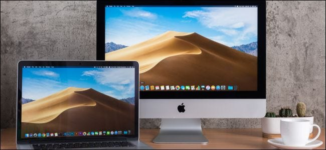 A MacBook next to an iMac on a wooden desk.