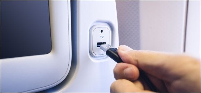 A hand plugging a USB cord into a charging port on the back of an airline seat.
