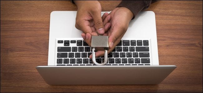 Hands holding a lock over a MacBook