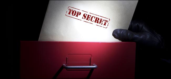 """Una mano sacando un documento marcado como """"Top Secret"""" de un archivador."""