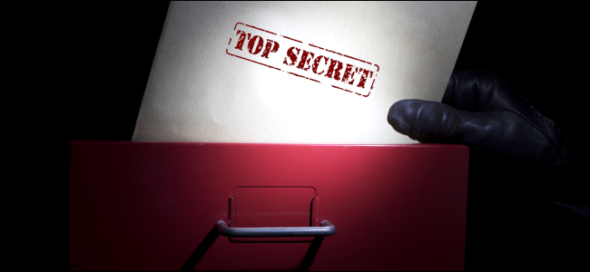 "A hand pulling a document marked ""Top Secret"" out of a filing cabinet."