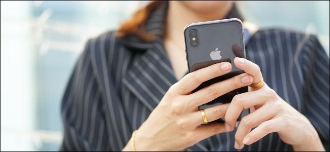 A woman' hands holding an iPhone X.