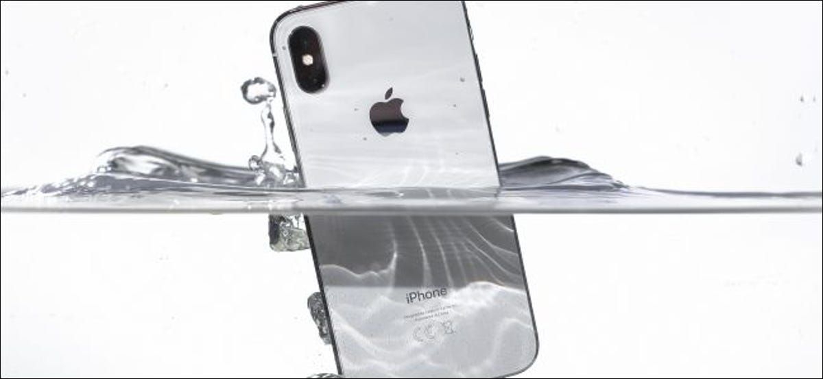 Submerging a silver iPhone X underwater.