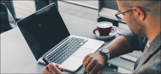 Un hombre en una mesa en un café mirando su reloj con su computadora portátil abierta frente a él.