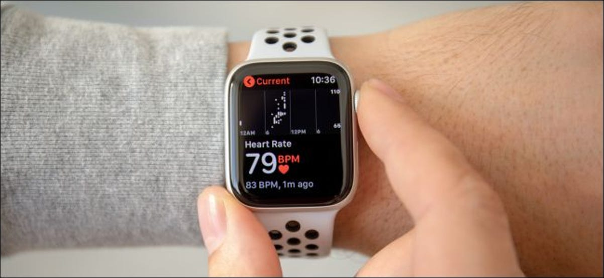 A man's hand checking the heart rate monitor on an Apple Watch Series 4.