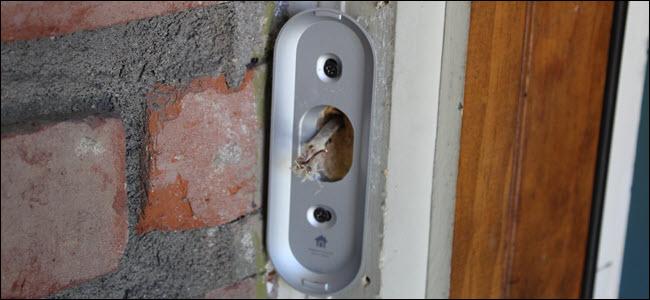 Un soporte de montaje Nest Hello unido al marco de una puerta con cables que se asoman.