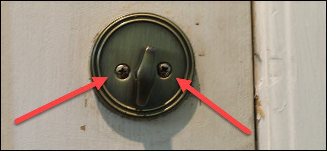 A standard thumbturn on a lock,with two red arrows pointing to two screws.