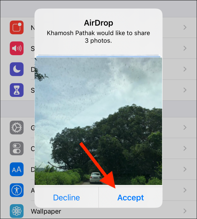 "An AirDrop request to share photos; your contact has to tap ""Accept"" to start the file transfer."