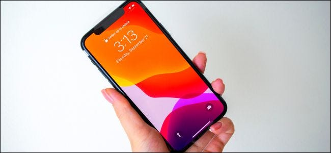 A hand holding up an iPhone 11 Pro.
