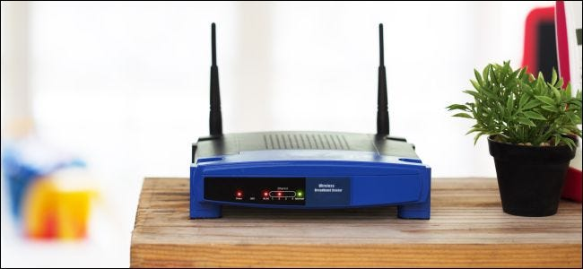 An old wireless router on a table in a home.