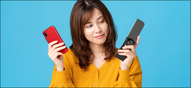 A woman holds up a flip phone and an iPhone. She looks toward the flip phone---toward a long departed era...