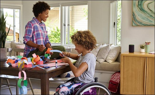 Uma criança em uma cadeira de rodas fazendo artesanato com a mãe em uma mesa com um Amazon Echo nas proximidades.