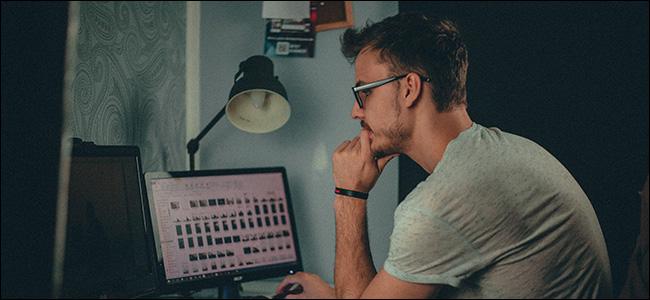 Man Sitting at Computer Looking at Files