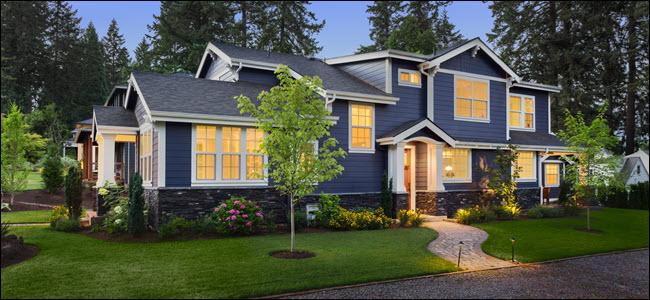 Exterior de uma casa azul e branca de dois andares ao entardecer com as luzes internas acesas.
