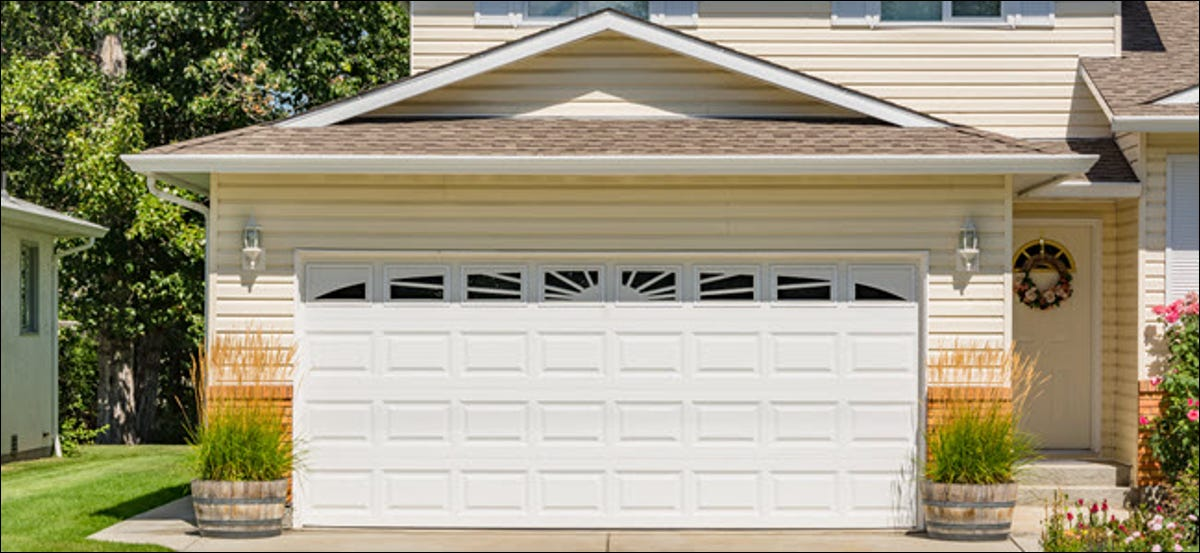 Family house with wide garage door and concrete driveway in front