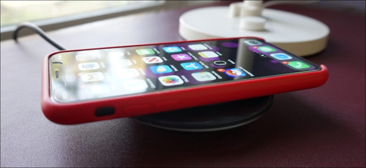 An iPhone sitting on a wireless charger.