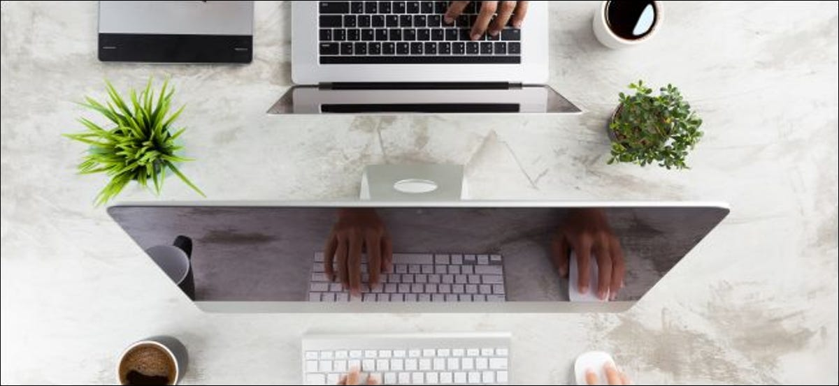 One person's hands using a Mac while another person's hands use a MacBook Pro across the table.