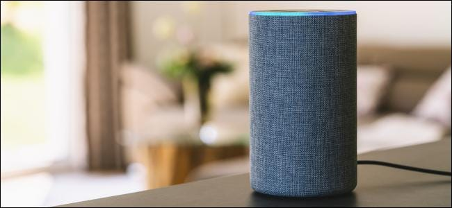 A grey Amazon Echo in the middle of a living room.