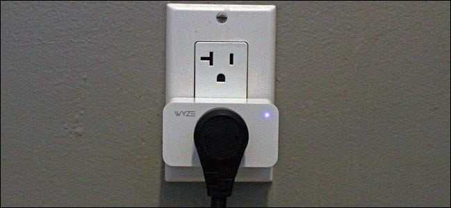 A Wyze smart plug in an outlet with a device plugged into it.